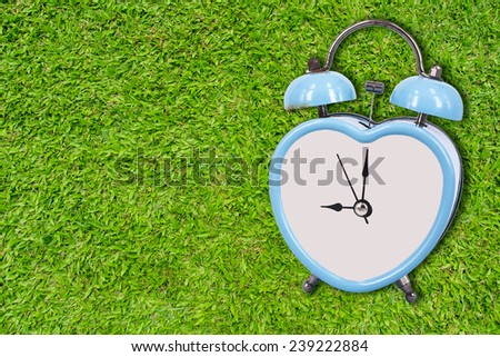 blue old retro clock on green grass background ,abstract background to memory of last time. - stock photo