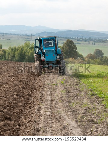 blue old tractor in autumn on field