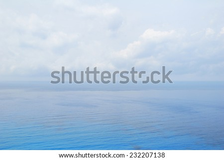 Blue open sea water under cloudy sky - stock photo