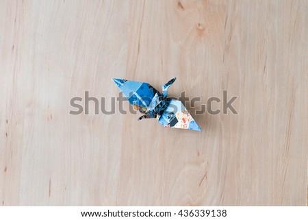 blue origami paper bird, crane on wooden background - stock photo