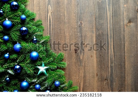 Blue ornament balls with star Christmas tree on wooden background - stock photo
