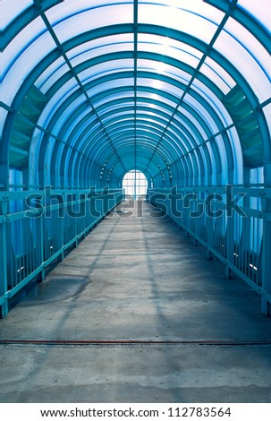 Blue overhead pedestrian crossing with sunlight - stock photo