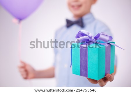 Blue package with lilac ribbon held by a boy - stock photo