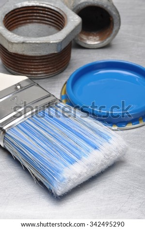 Blue paint can lid with brush and metal plumbing parts on grey metal background - stock photo