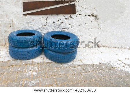 blue painted car tires near a white wall
