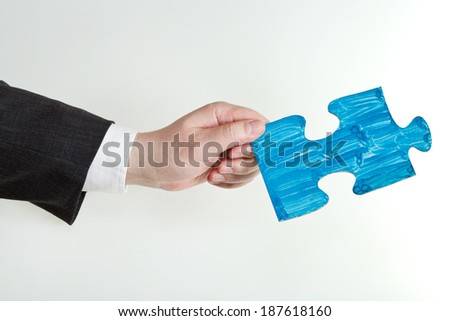 blue painted puzzle piece in male hand on grey background