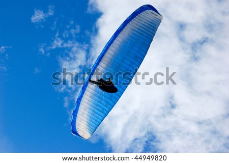 Blue Paraglider on blue sky with feather clouds over the camera - stock photo