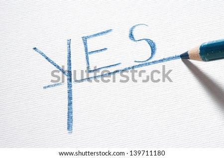 Blue pastel pencil writing the word YES - stock photo