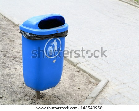 Blue pastic garbage bin or can and bench on street - stock photo