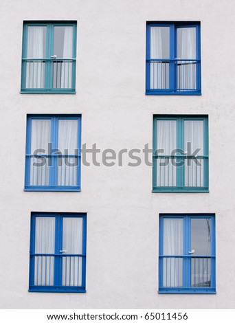 Blue patio doors and window, in a pattern on a white building wall.  Taken in vertical format. - stock photo