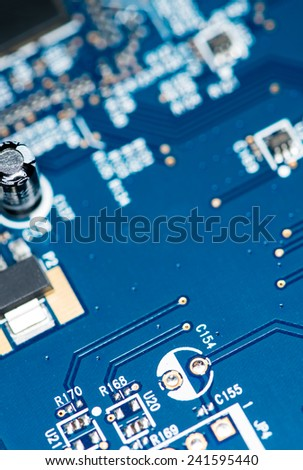 Blue PCB with a lot of elecric components as detailed macro shot - stock photo