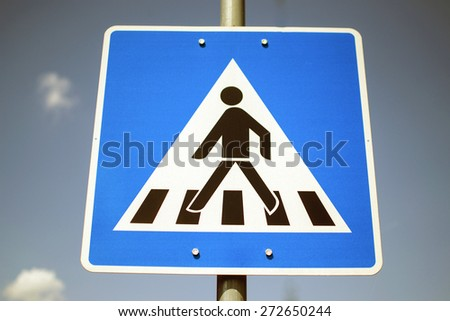 Blue pedestrian crossing sign against blue sky - stock photo