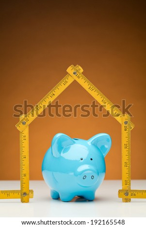 Blue piggy bank inside a house made of an old wooden yellow measurement tape, orange background. - stock photo
