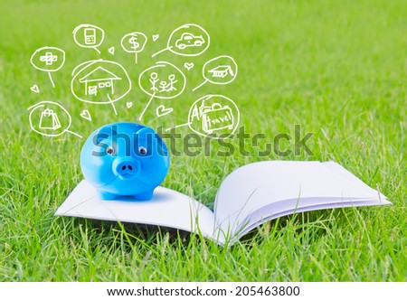 Blue piggy bank on booklet and icon design to represent the concept of saving money  - stock photo
