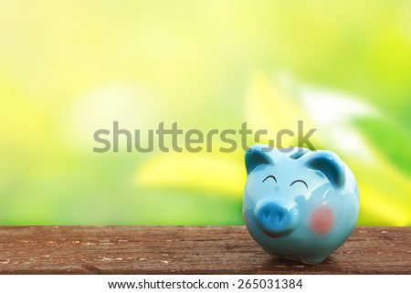 blue piggy bank on wooden table over blurred garden bokeh background. saving, money concept. - stock photo