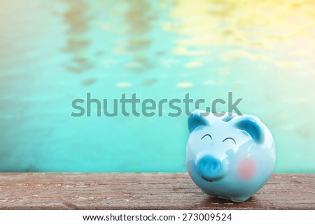 blue piggy bank on wooden table over blurred water background. saving,money concept. - stock photo