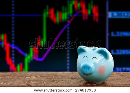blue piggy bank on wooden table over chart of stock share, abstract background to business ,money and saving concept. - stock photo