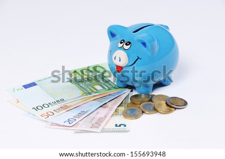 blue Piggy bank with Euro bills and Euro Coins - stock photo