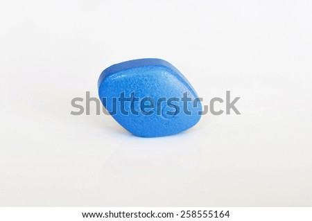 Blue pill for erectile dysfunction treatment, white background, close-up, shallow DOF - stock photo