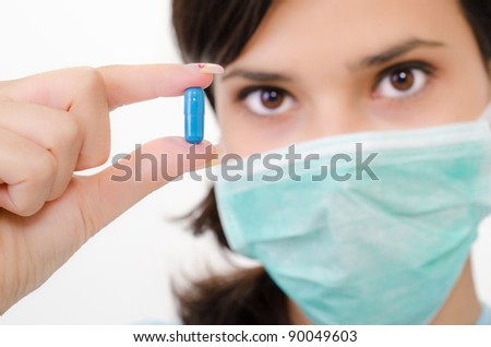 Blue pill in a woman's hand, isolated an a white background - stock photo