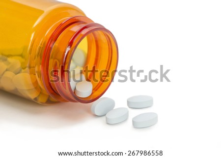 Blue pills spill from orange prescription medication bottle on white background. - stock photo