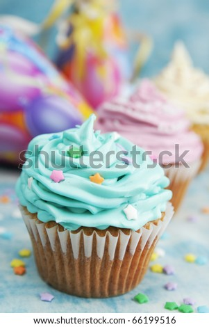 Blue, pink and white cupcake in a row with hat in background - stock photo