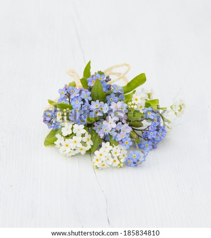 blue, pink, and white forget-me-nots bouquet tied with raffia on a white wooden board