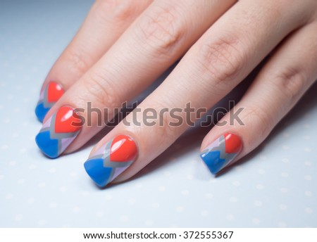 Blue pink nail Polish on long nails on a white background.