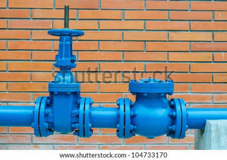 blue pipe line with blue valve  on brick wall - stock photo