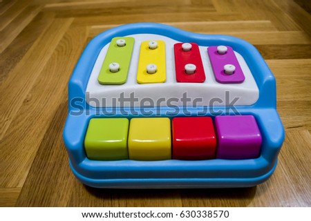 Blue plastic baby piano toy on wooden floor. Colorful children music keyboard.
