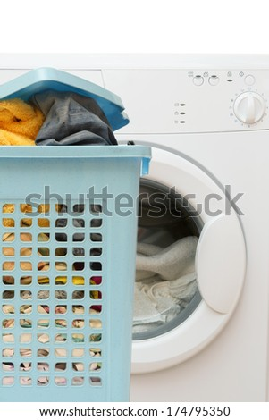 Blue plastic basket full of clothes and clothes washer - stock photo
