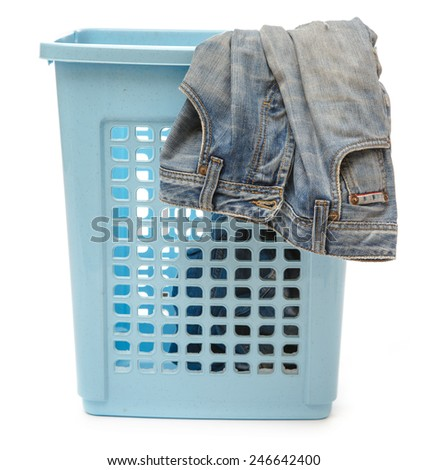 Blue plastic basket with dirty jeans on white - stock photo