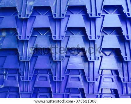 Blue Plastic crates stacked packing containers background on front view . - stock photo