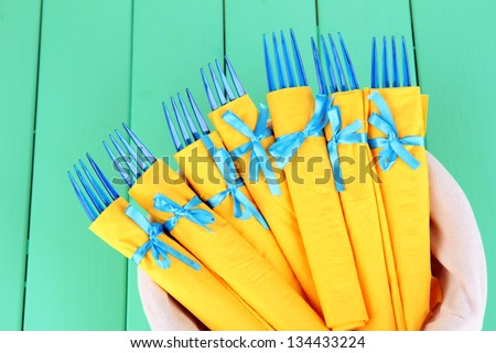 Blue plastic forks wrapped in yellow paper napkins, in basket, on color wooden background