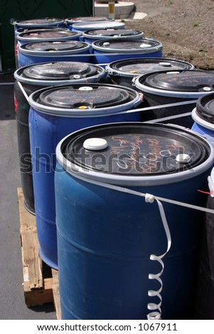 blue plastic 55 gallon drums full of various flammable waste at a recycling plant - stock photo