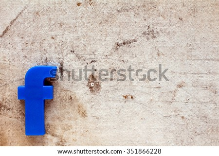 Blue plastic letter F on canvas background with copy-space - stock photo