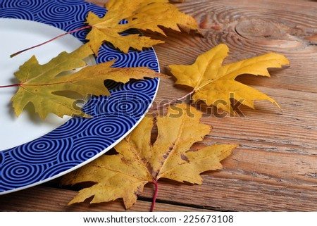 Blue plate and maple leaves on a wooden table - stock photo