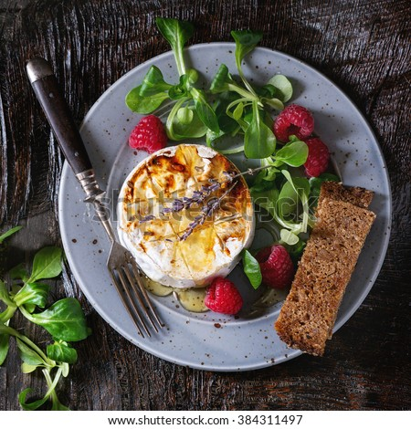 Blue plate with grilled goat cheese served with liquid honey, lavender, raspberries, wholegrain toast and green salad. With vintage fork over wooden table. Dark rustic style. Flat lay. Square image