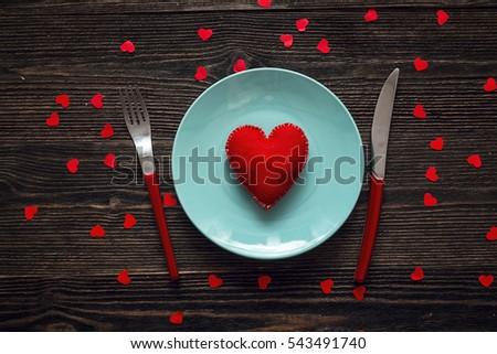 Màu xanh tấm bằng trái tim, ngã ba màu đỏ và con dao trên một chiếc bàn gỗ đen tối.  Ngày Bàn ăn lãng mạn đặt Valentine.