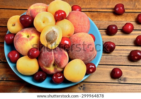 Blue plate with mix fruits on table - stock photo