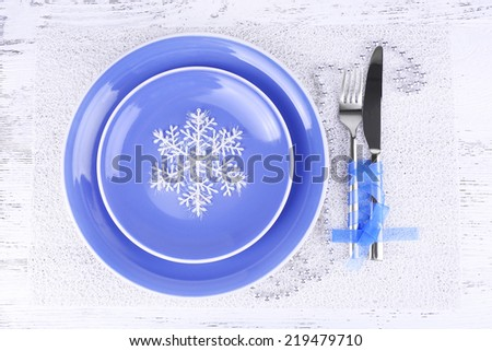 Blue plates, knife, fork, napkin and Christmas decoration on wooden background - stock photo