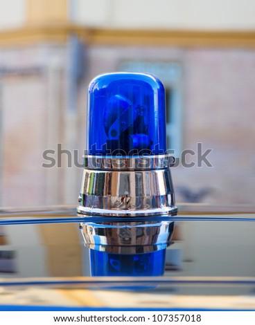 blue police light on an old police car - stock photo