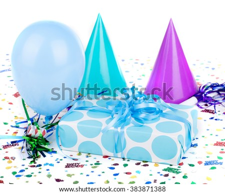 Blue polka dot birthday present with party decorations - stock photo