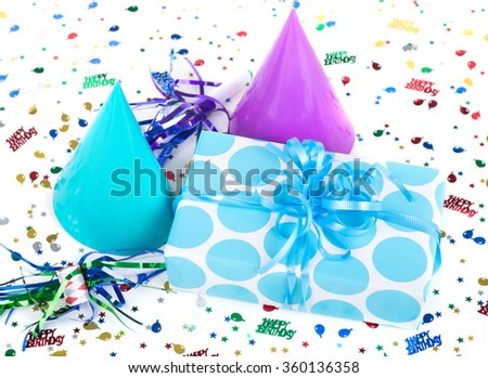 Blue polka dot present with birthday hats, noisemakers and confetti on a white background