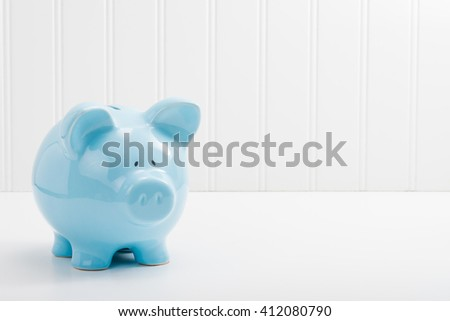 Blue porcelain piggybank with ample copy space. - stock photo