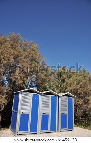 blue portable toilets near the beach - stock photo