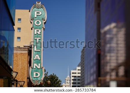 Blue Portland sign from 30's on brick building from distance in Portland, Oregon, USA with clear blue sky - stock photo