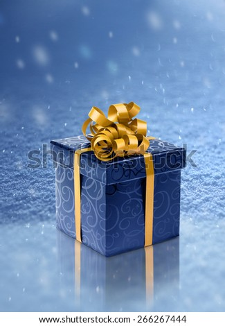 Blue present box on ice in realistic snowfall background - stock photo