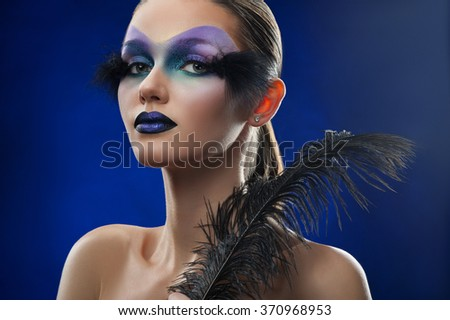 Blue pride. Studio shot of a beautiful confident female model posing wearing blue feather makeup against blue background looking to the camera