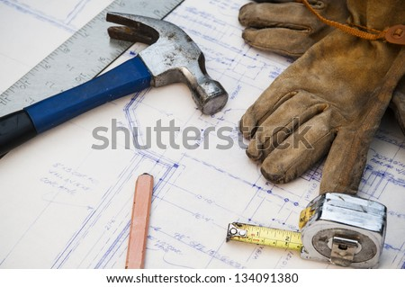 blue prints at a work site with tools and gloves - stock photo